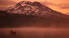 Man rows canoe at sunrise Stock Footage