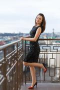 Attractive young beautiful girl wearing classical black dress posing on the - stock photo