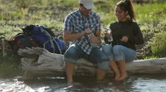 Backpackers take break by stream and drink water Stock Footage