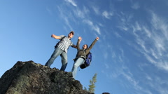 Backpackers celebrate on top of rock Stock Footage