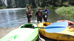Three kayakers prepare gear, kayaks in foreground - stock footage