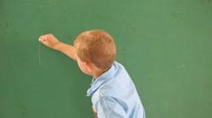 Boy writes alphabet on chalk board - stock footage