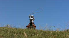 Cowboy rides over hill swinging lasso, slow motion Stock Footage
