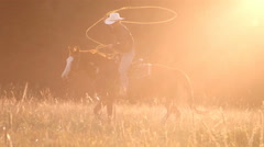 Cowboy roping at sunset, slow motion Stock Footage