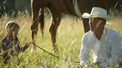 Father and son cowboys sit in grass taking break Stock Footage