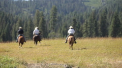 Three cowboys ride off into the wilderness Stock Footage