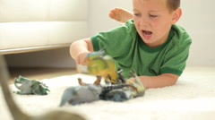 Boy playing with toy dinosaurs - stock footage
