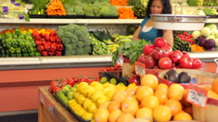 Grocery store worker helps woman shopping for produce Stock Footage