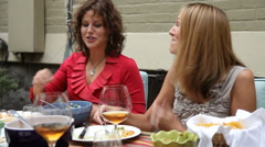 Two women talking and eating at outdoor dinner party Stock Footage