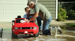Grandfather helping grandson wash car Stock Footage