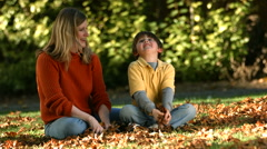 Mom and son playing in fallen leaves Stock Footage