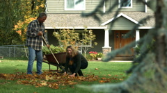 Couple playing in fallen leaves - stock footage
