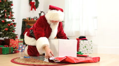 Santa Claus wraps Christmas gift Stock Footage