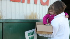 Mother teaching young daughter how to recycle - stock footage