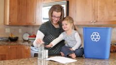 Mother and young daughter in kitchen recycling - stock footage
