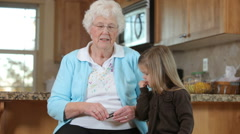 Senior woman talks on phone with Great Granddaughter Stock Footage