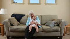 Elderly Great Grandmother sitting with baby Stock Footage