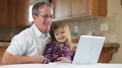 Young girl working on laptop computer with Grandfather - stock footage
