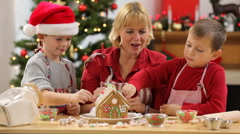 Mother and sons build Gingerbread house Stock Footage