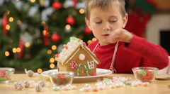 Young boy builds gingerbread house Stock Footage