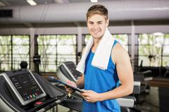 Portrait of trainer holding clipboard on treadmill - stock photo
