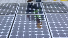 Contractor on industrial rooftop checks solar panels Stock Footage