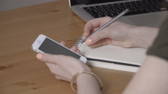 Woman hand writing in agenda and checking on a mobile phone on a desk. Stock Footage