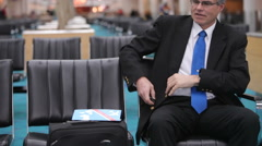 Mature business man takes a nap in airport lobby Stock Footage