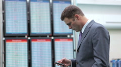 Business man at airport checks airline departure screens Stock Footage