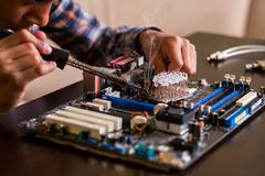 Kid fixes motherboard on table. - stock photo