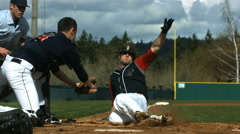Baseball player slides is safe at home plate, slow motion Stock Footage
