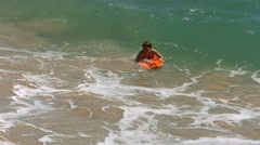 Two young boys boogie boarding in ocean, slow motion Stock Footage