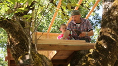 Father and son working on treehouse together Stock Footage
