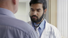 Doctor listening to senior male's heart rate Stock Footage
