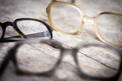 Old nerdy hornrims or eye glasses on wooden table Stock Photos