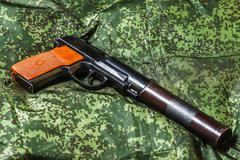 semi-automatic silenced pistol on pixel camouflage background - stock photo