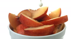 Pouring cream over bowl of fresh peaches, slow motion Stock Footage