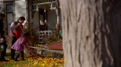 Family raking leaves Stock Footage