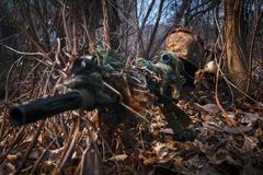 Sniper wearing camouflage suit with rifle hide in the woods - stock photo