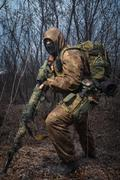 Sniper wearing camouflage suit with rifle walk in the woods - stock photo