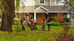 Asian family raking leaves Stock Footage