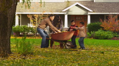 Asian family playing in falling leaves Stock Footage