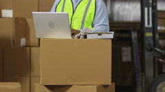 Workers look at laptop computer in shipping warehouse Stock Footage