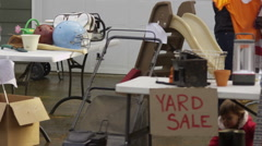 Women shop for clothing at yard sale Stock Footage