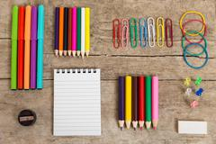 Colorful office desk with a notepad, pencins and other equipment Stock Photos