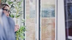 4K Fashion designer taking a break, drinking hot drink next to window - stock footage