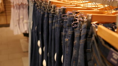 Hangers with a fashionable jeans clothes in store boutique - shopping discounts Stock Footage