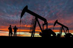 Silhouettes of Pumpjacks and Oil Workers - stock photo