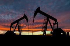 Dramatic Sky Over Pumpjack Silhouettes - stock photo