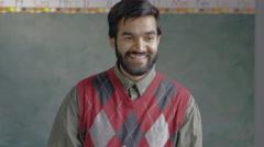 Male teacher in front of a chalkboard in a classroom - stock footage
